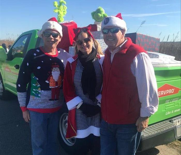People standing in front of a servpro truck dressed in christmas attire